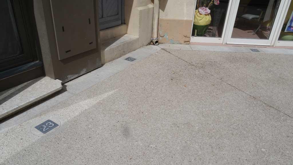 Traverses - détail d'incrustation des numéros d'habitations dans le béton des sols